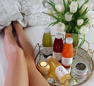 Detox Delight Juices with flowers and a girl lying in bed
