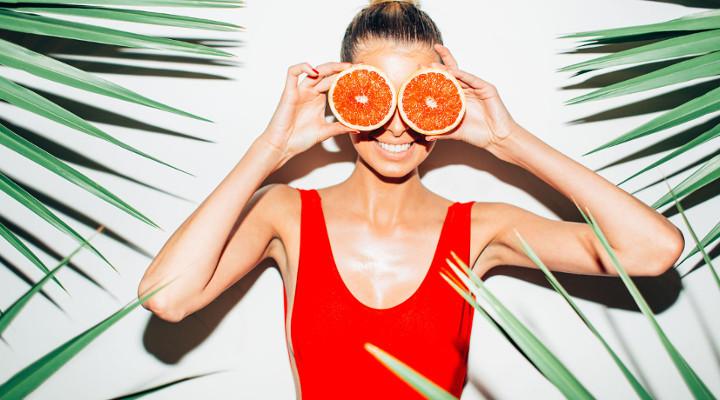Frau in Badeanzug mit Grapefruits